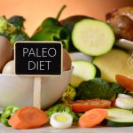 closeup of a signboard with the text paleo diet on a table full of different raw vegetables, a bowl with some chicken eggs and a chicken
